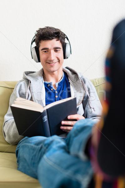 Jeune homme couché canapé lecture livre Photo stock © Kzenon