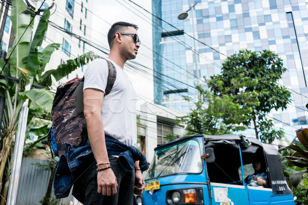 Young man wearing sunglasses and backpack during vacations in In Stock photo © Kzenon