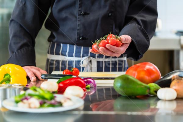 Szakács vág paradicsomok saláta hotel konyha Stock fotó © Kzenon