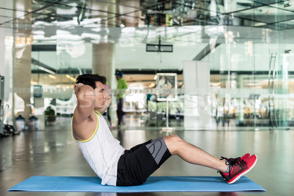 Young man sitting down while doing crunches for the abdominal muscles Stock photo © Kzenon