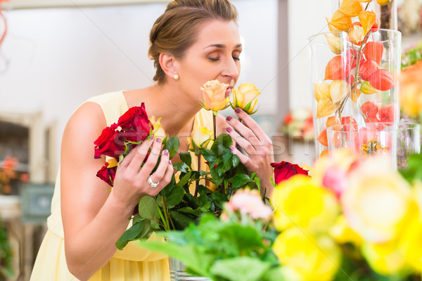 Florist woman smelling at roses Stock photo © Kzenon