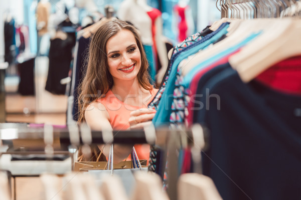 Woman browsing through dresses on rack in fashion store Stock photo © Kzenon