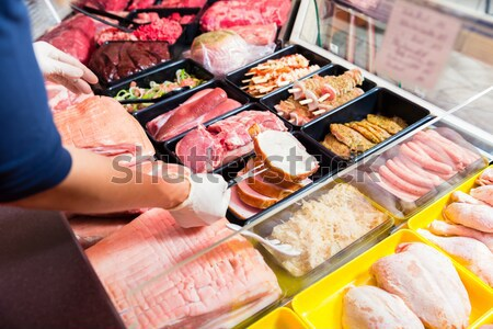 Sales woman in butchery holding sausage wrapped in paper Stock photo © Kzenon