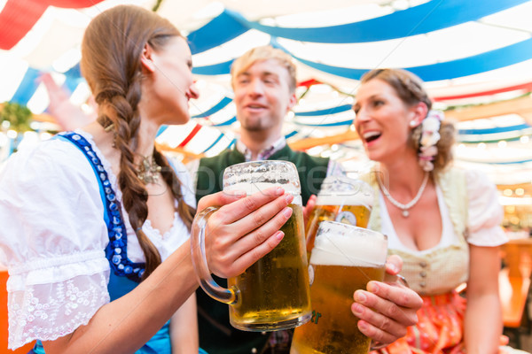 Friends with beer glasses at Bavarian beer tent Stock photo © Kzenon