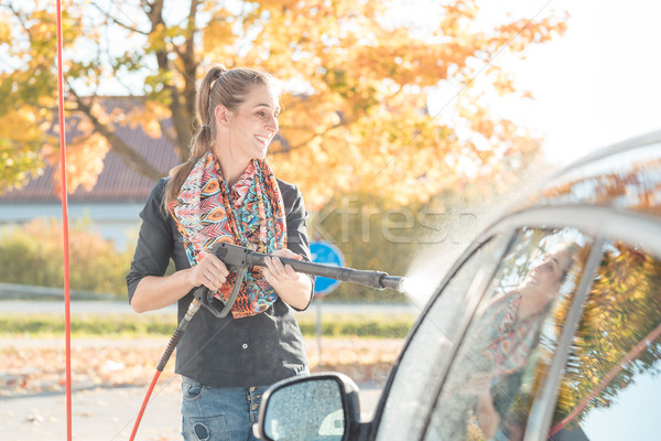 Woman using high pressure nozzle to clean her car Stock photo © Kzenon