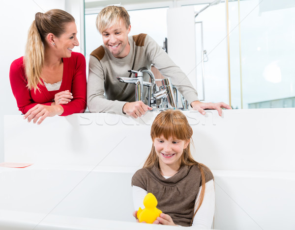 Funny girl looking at her parents while sitting in a bathtub i Stock photo © Kzenon
