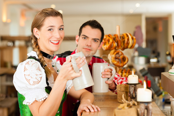 Young couple in traditional Bavarian Tracht in restaurant or pub Stock photo © Kzenon