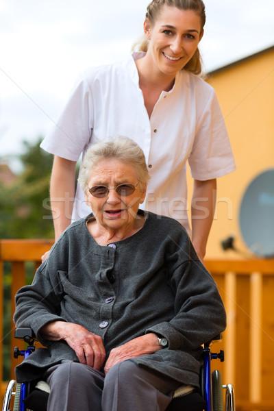 Young nurse and female senior in a wheel chair Stock photo © Kzenon