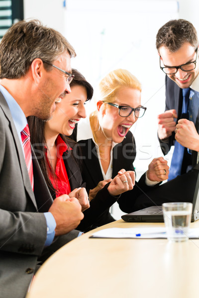 Business people looking at laptop with success Stock photo © Kzenon