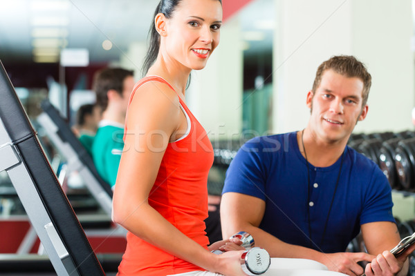 Stock photo: woman and Personal Trainer in gym, with dumbbells