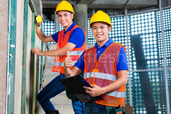 Asian worker controlling building on construction site Stock photo © Kzenon