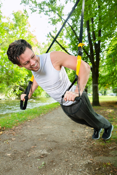 man doing suspension trainer sling sport Stock photo © Kzenon