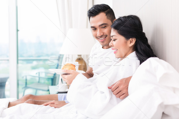 Stock photo: Asian couple lounging in bed at morning