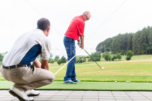 Golf trainer working with golf player on driving range Stock photo © Kzenon
