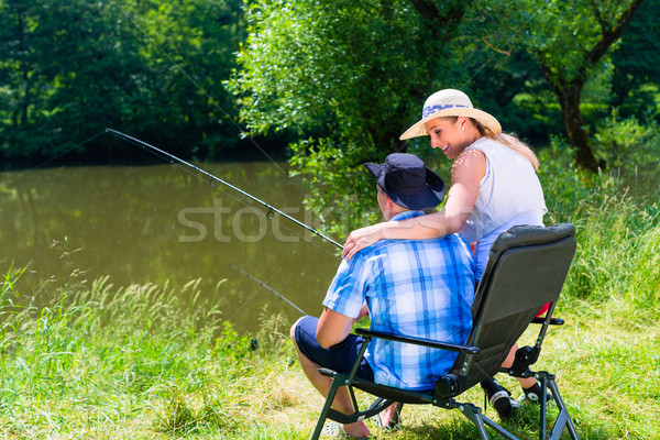 Man and woman fishing with angle together at river shore Stock photo © Kzenon