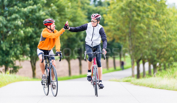 Racing cyclists after sport and giving high five Stock photo © Kzenon