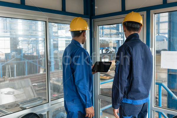 Two workers wearing hard hats while using a tablet PC Stock photo © Kzenon