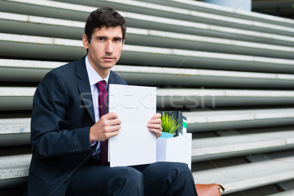 Young unemployed man sitting on stairs after being fired or afte Stock photo © Kzenon