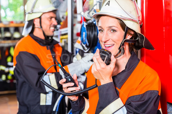 Stock photo: Chief fire fighter  checking radio set