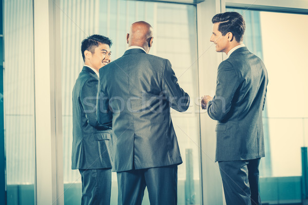 Multi ethnic business team reporting to Indian CEO discussing in Stock photo © Kzenon