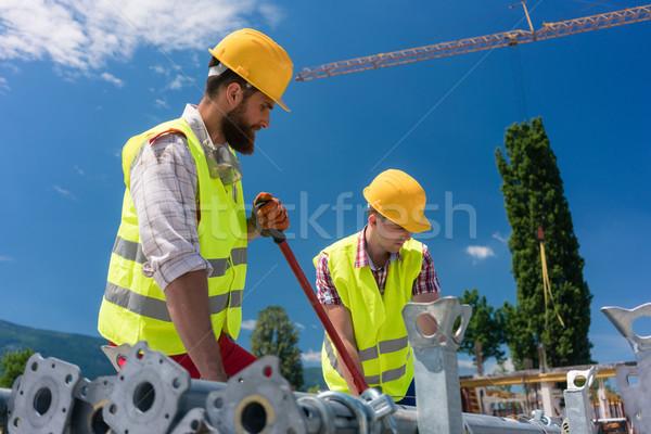 Two efficient blue-collar employees building a metallic scaffold Stock photo © Kzenon