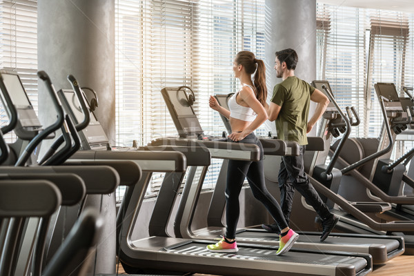 Young man and woman smiling while running side by side on electr Stock photo © Kzenon