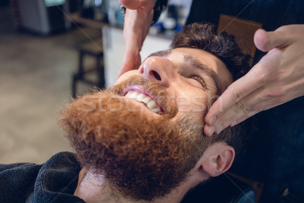 Young bearded man smiling during a relaxing temple massage Stock photo © Kzenon
