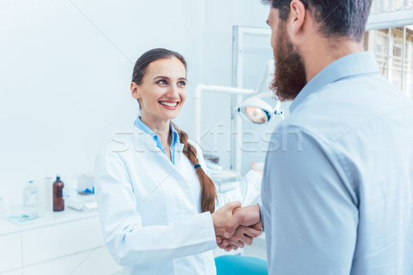 Portrait of a reliable and cheerful dentist shaking the hand of a patient Stock photo © Kzenon