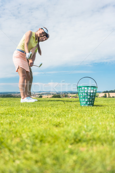 Young woman practicing the correct move during golf class with Stock photo © Kzenon