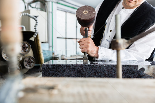 Stock photo: Stone mason working on tombstone in workshop