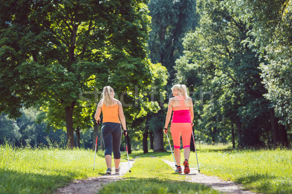 Mother and daughter doing Nordic Walking Stock photo © Kzenon