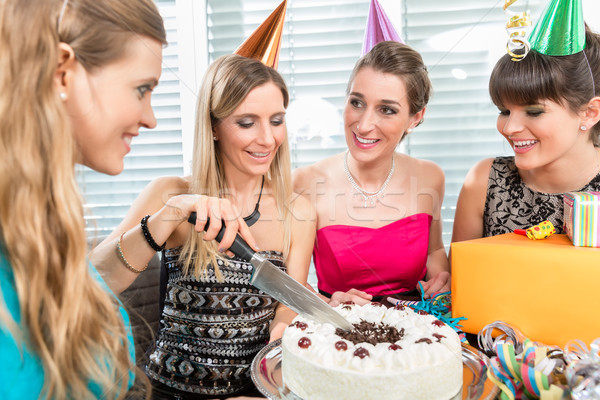 Woman blowing out candles on her birthday cake while celebrating Stock photo © Kzenon
