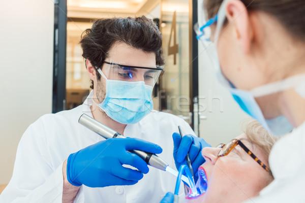 Dentists hardening toot crown with UV light  Stock photo © Kzenon