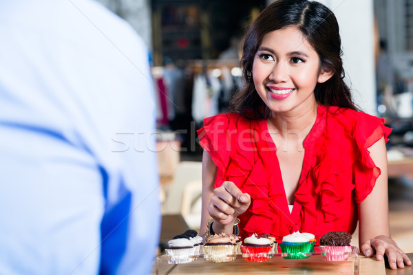 Portrait of a cheerful Asian woman ordering cupcakes in a cool cafe Stock photo © Kzenon