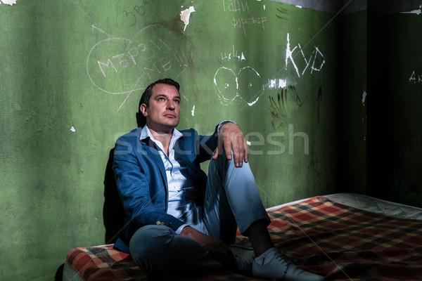 Depressief jonge man vergadering matras donkere gevangenis Stockfoto © Kzenon