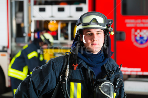 young fireman in uniform in front of firetruck Stock photo © Kzenon