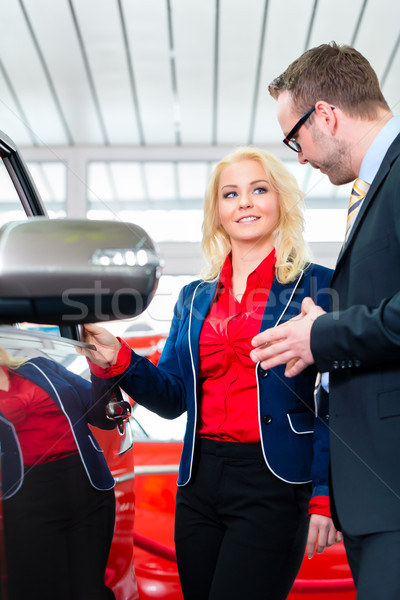 Woman looking at car in auto dealership Stock photo © Kzenon