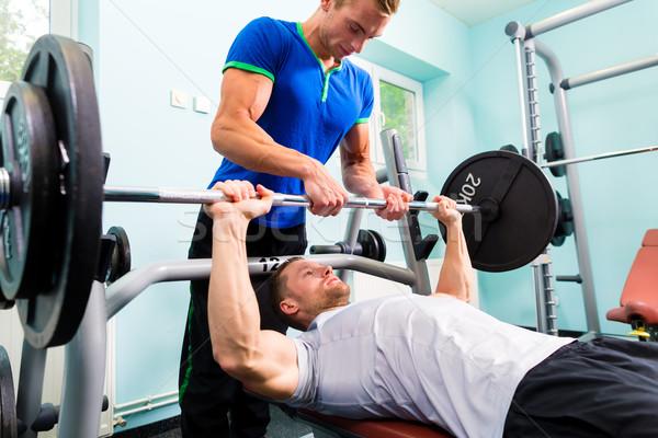Men in sport gym training with barbell for fitness Stock photo © Kzenon