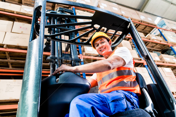 Forklift driver in industrial logistics warehouse Stock photo © Kzenon