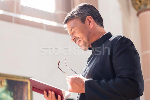 Católico sacerdote lectura Biblia iglesia hombre Foto stock © Kzenon