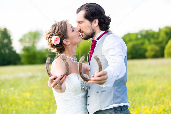 Wedding couple showing horse shoe Stock photo © Kzenon