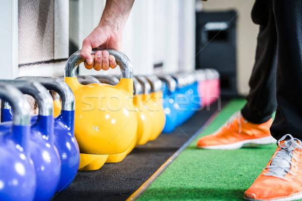 Man lifting kettlebell from floor doing sport Stock photo © Kzenon