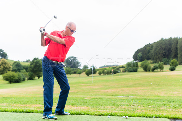 Golfer training his swing on golf driving range Stock photo © Kzenon