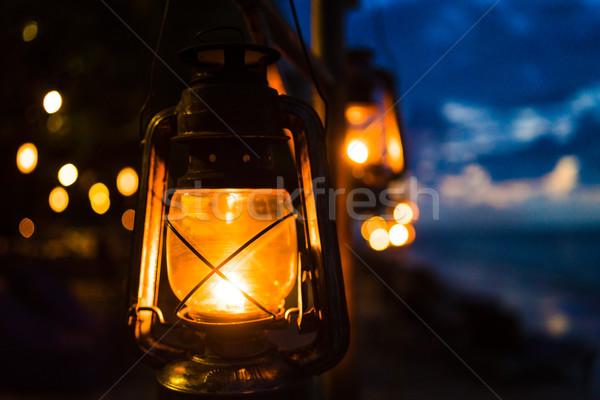 Sunset on an island beach with lanterns illuminating the scene Stock photo © Kzenon