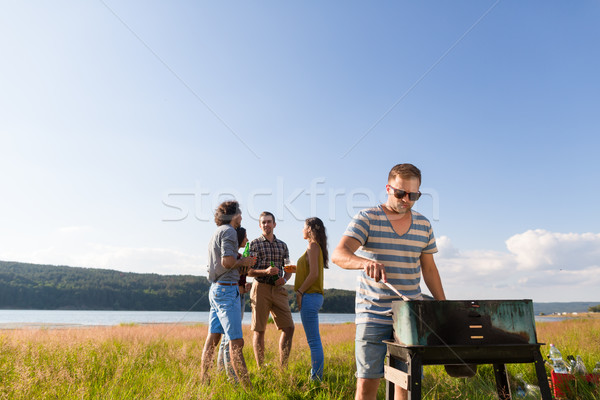 Clique of young people making BBQ at lake Stock photo © Kzenon