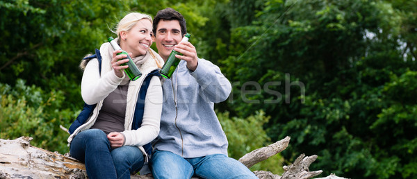 Lovers in vacation sitting at waterside clinking beer bottles Stock photo © Kzenon