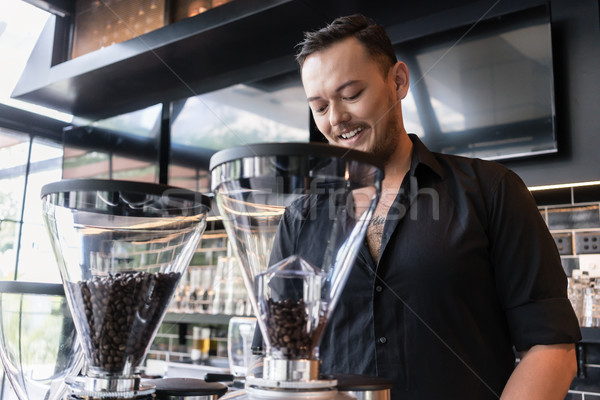 Happy young man preparing espresso while working as barista in a Stock photo © Kzenon