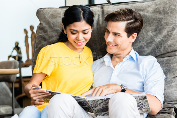 Stock photo: Couple sitting in chair of furniture store