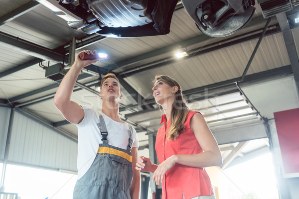 Reliable auto mechanic checking the car of a woman in a modern a Stock photo © Kzenon
