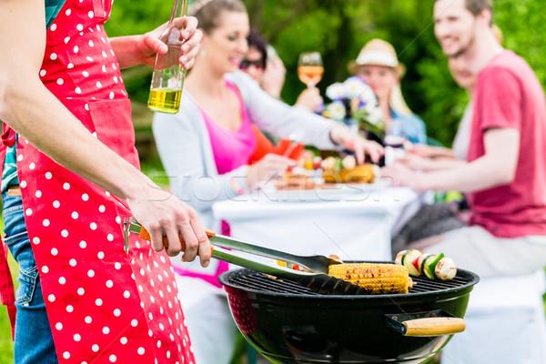 Homem grelhar carne legumes festa no jardim amigos Foto stock © Kzenon